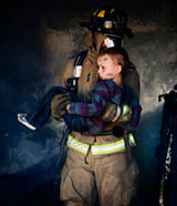 Image of a firefighter carrying a child from a smoke filled house